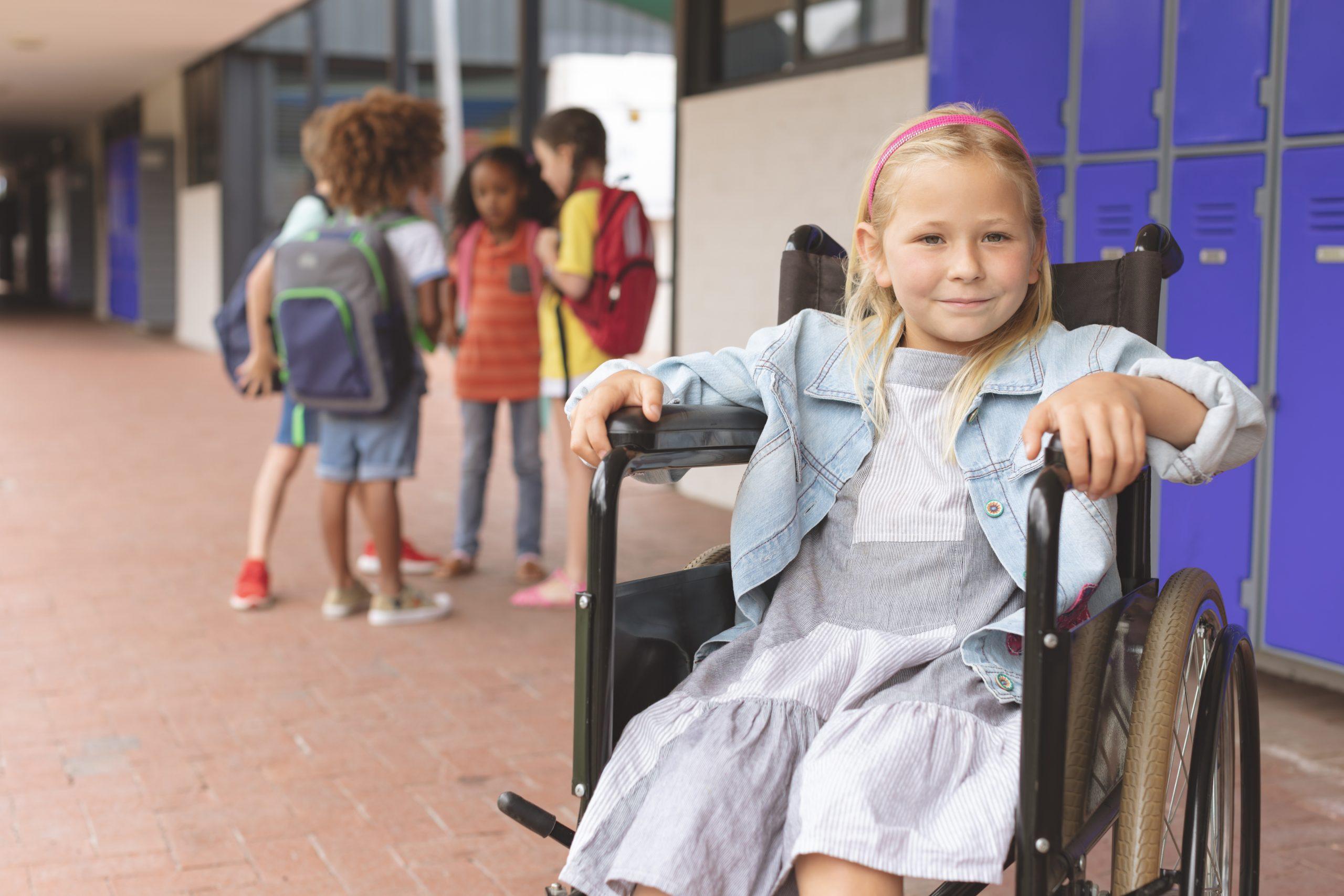 Front view of a schoolgirl sitting on wheelchair in corridor aginst school kids speaking together in background in outside corridor at school
